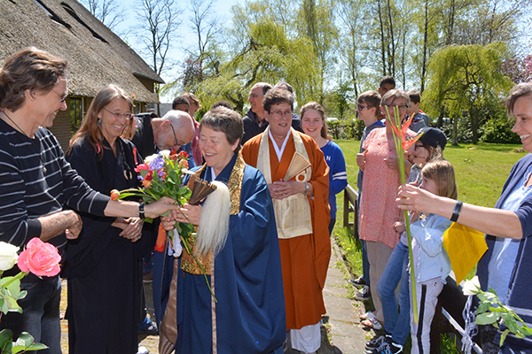 Zen-meester Tetsue roshi begroet met bloemen